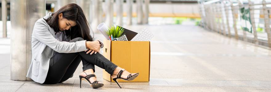 Mulher sentada no chão triste com uma caixa