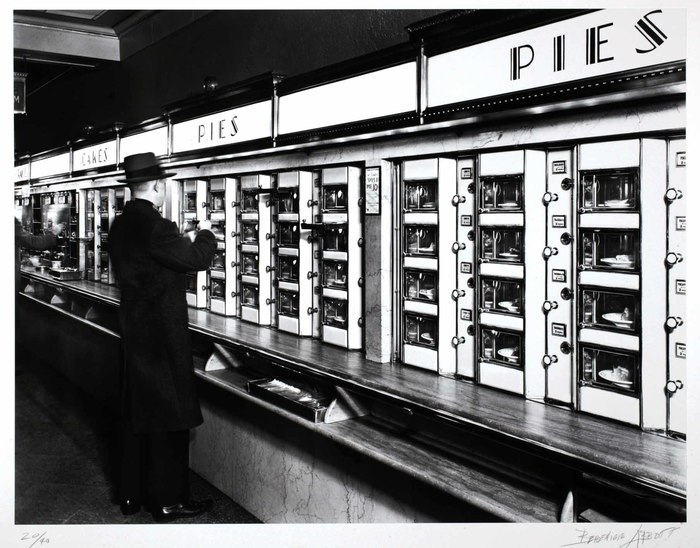 Black and white photo of customer choosing a pie at an early 20th century automat