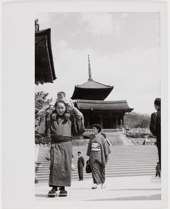 People in Japanese clothing walking in a Buddhist Temple complex