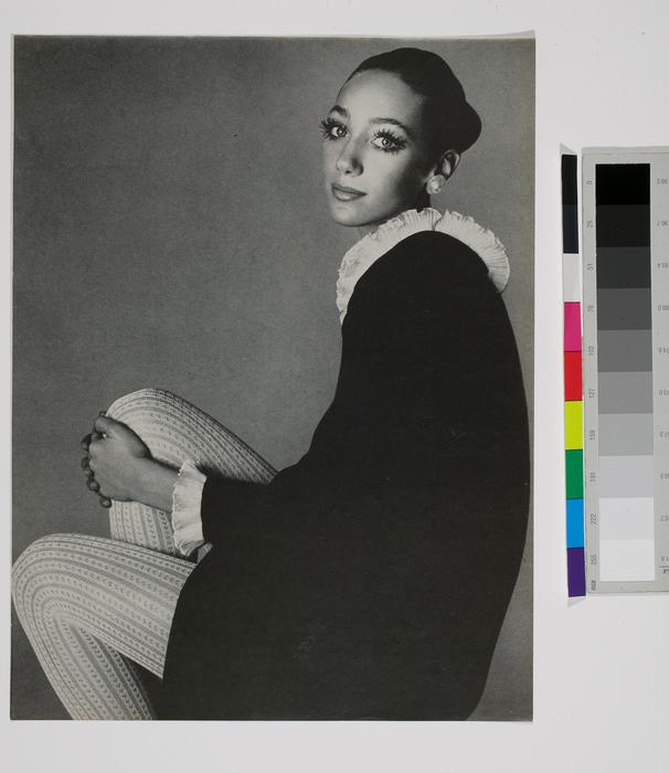 [Fashion model seated wearing black dress and white stockings]