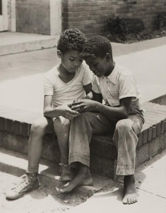 [Two boys examining object]