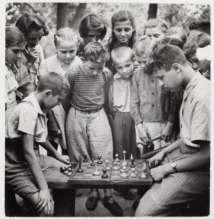 [Two boys play a game of chess on a park bench with crowd of spectators looking on, Moscow]