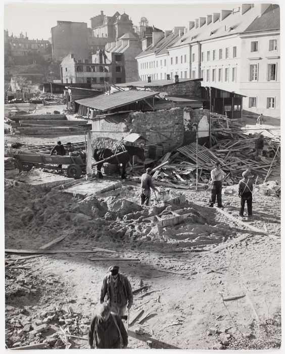 Workers working on a construction site with reconstructed buildings