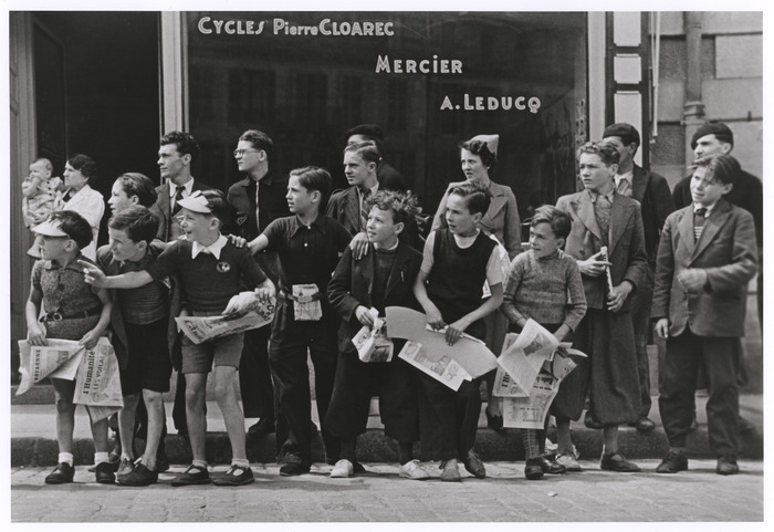 [Watching the Tour de France in front of the bicycle shop owned by Pierre Cloarec, one of the cyclists in the race, Pleyben, France]