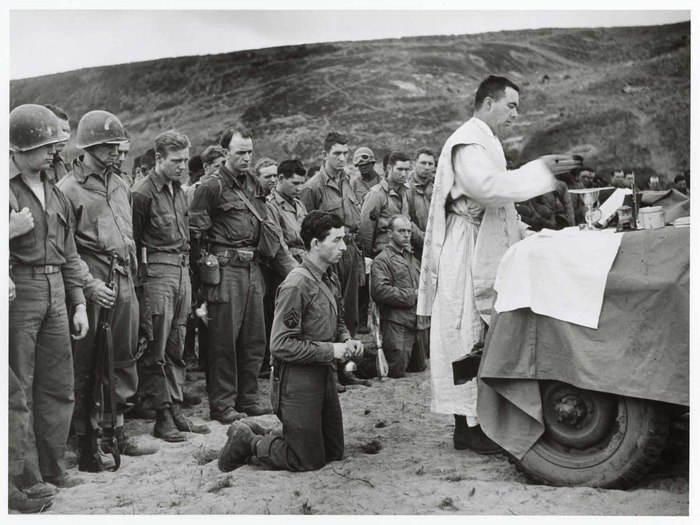 [Using the hood of a jeep as an altar, a Roman Catholic chaplain saying mass at the inauguration of an American cemetery, Omaha Beach, Normandy]
