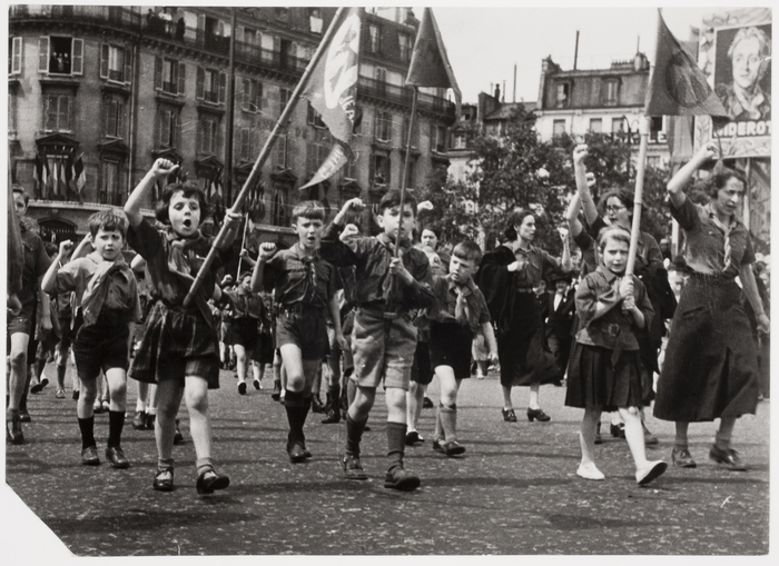 [Young girls and boys parading in the streets on May Day, doing the Republican salute and holding flags, Paris]