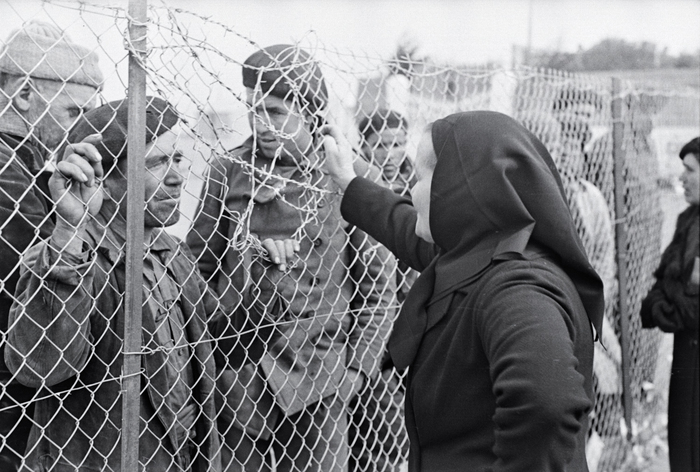 [Man talking to a woman through a fence at an internment camp for Spanish refugees, Argelès-sur-Mer, France]