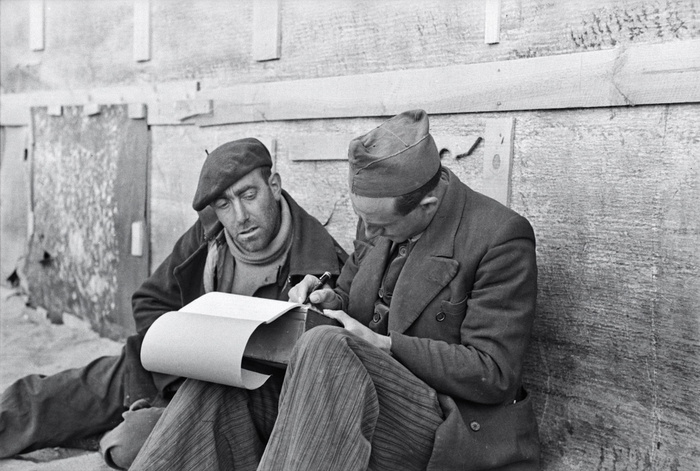 [Two men writing a letter at an internment camp for Spanish refugees, Le Barcarès, France]