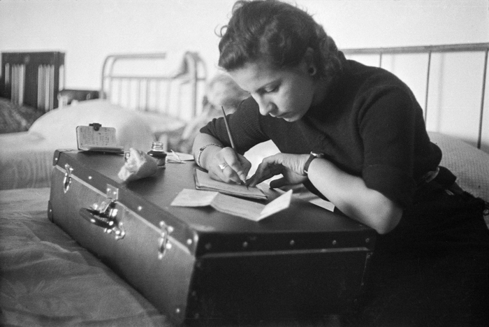 Young woman writing a letter on a suitcase at a refugee center