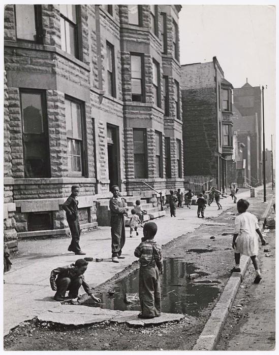 [Children playing on sidewalk near puddle, Chicago]