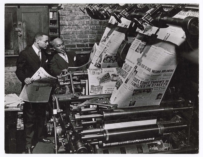 [Newspaper founder Robert S. Abbot checking copy fresh from printing press at Chicago Defender]