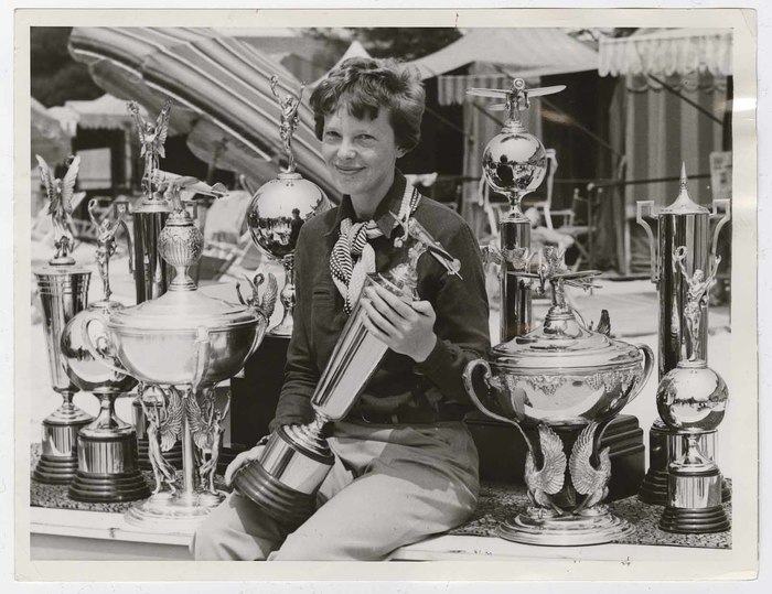 [Amelia Earhart surrounded by trophies]