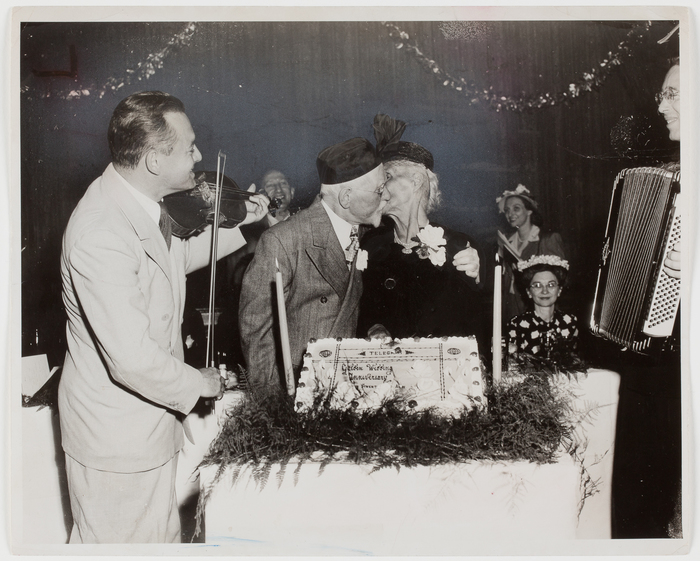 [Isidore Bass kissing his wife at a party for couples who have been married at least 50 years, New York]