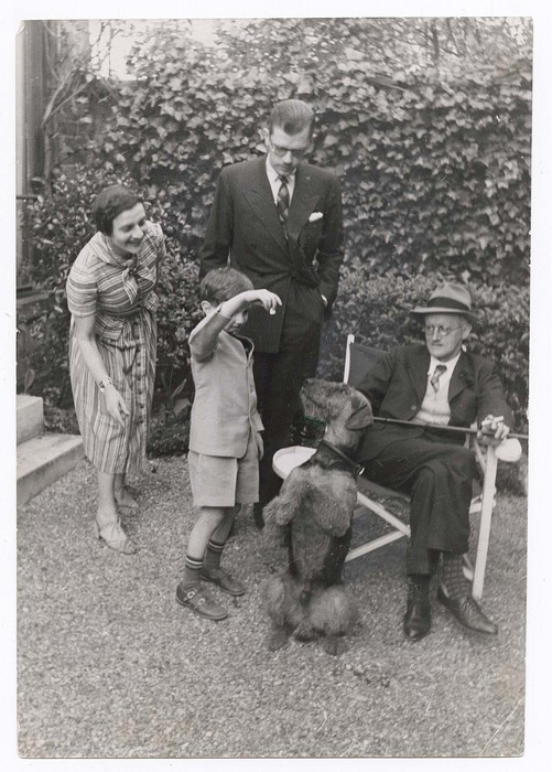 Three generations of Joyces.  James Joyce, seated, Giorgio standing, and Stephen playing with Schiap the dog Schiaparelli gave him, while Helen Joyce (Giorgio's wife looks on).  Taken in the garden of Giorgio's house in Paris