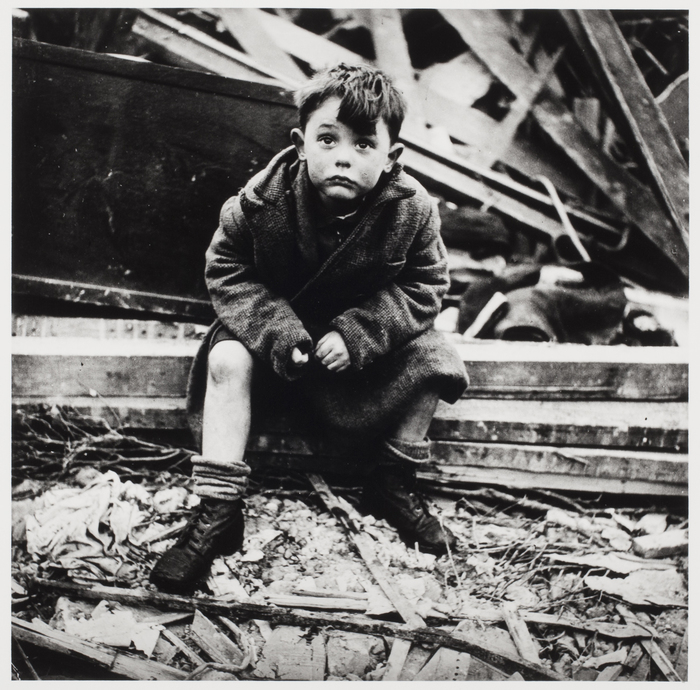 [Boy sitting in the rubble of his home where his parents lie buried after a V2 bomb hit, London]