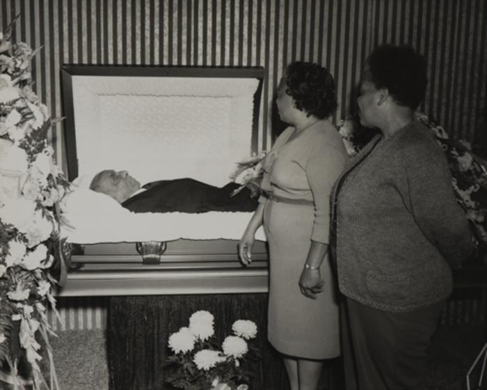 [Two women viewing open casket]