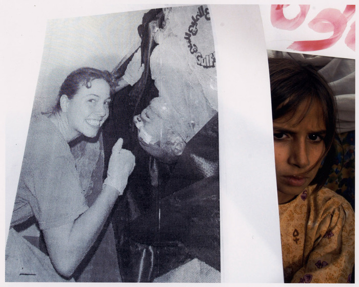A Pakistani girl holds a photograph showing a US soldier smiling beside the body of an Iraqi prisoner during a protest of the Citizens Peace Committee, a Non Government Organization (NGO) in Islamabad.