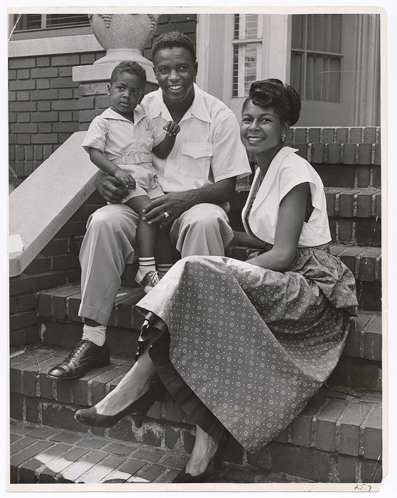 [Brooklyn Dodger baseball star Jackie Robinson holding his young son Jackie Jr. on his lap as he sits with his wife Rachel on front steps of their home]