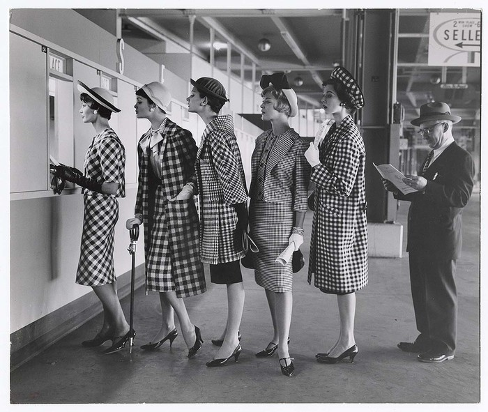 [Women wearing checked outfits, waiting to place bets at racetrack]