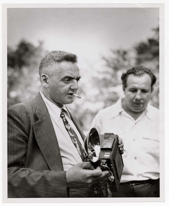 [Portrait of Weegee (Arthur Fellig) holding camera at demo on crime photography]