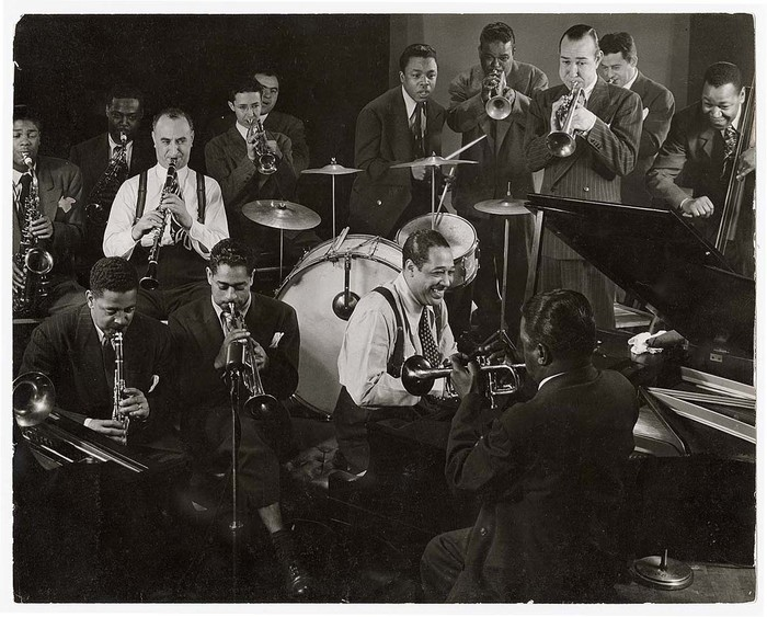[Duke Ellington at piano, Dizzy Gillespie (fore, 2L) on trumpet and behind him Mezz Mezzrow on clarinet, surrounded by other unidentified musicians during jam session in studio of LIFE photographer Gjon Mili]