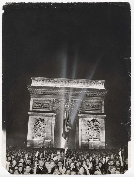 [Night view of a jubilant crowd of Parisians under the Arc de Triomphe celebrating the liberation of the city by the Free French forces commanded by Gen. De Gaulle]