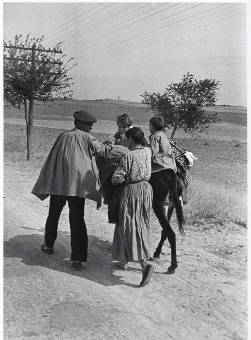 [Woman and men walking with their two children on a donkey, Spain]
