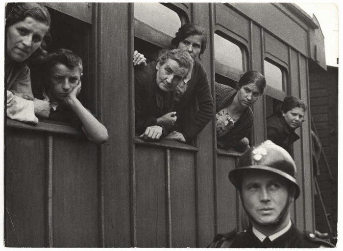 [Refugees in train windows, police officer in foreground, Spain-France border, near Cerbère, France]