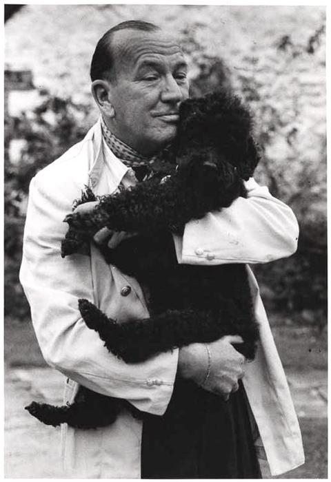 [Noel Coward at home, hugging his poodle]
