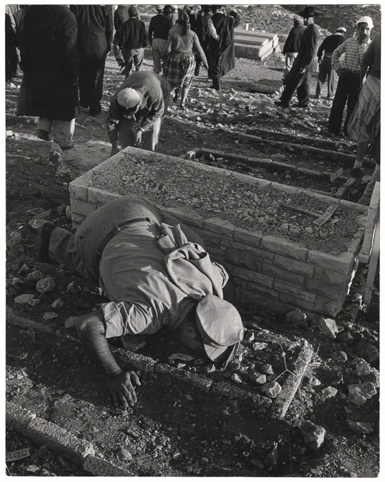 [Man in uniform kissing a grave while other people are leaving the cemetary, Jerusalem, Israel]