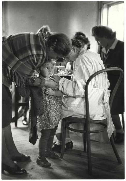 [Girl with her mother recieving medical attention, Poland]