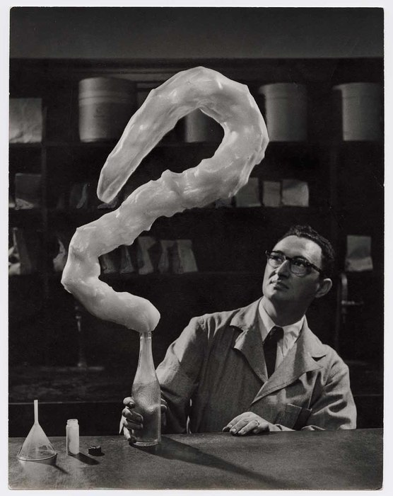[man holding bottle, S-shaped foam form emerging from it]