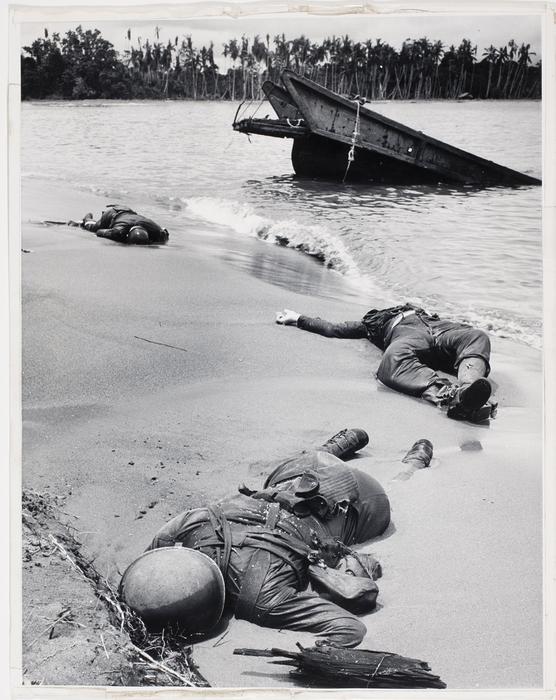 [Bodies of three dead American soldiers lying in the sand on shoreline near half sunken landing craft on Buna Beach]