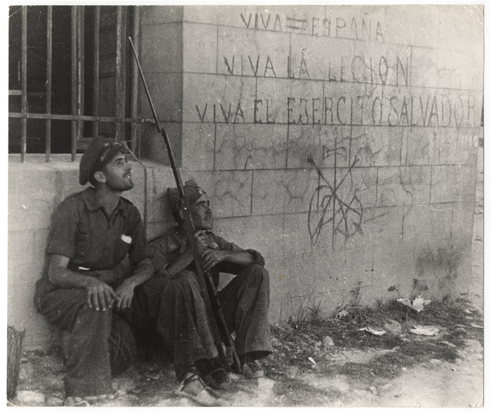 [Two Republican soldiers in front of wall with rightist slogans and symbols, Battle of Brunete, Spain]