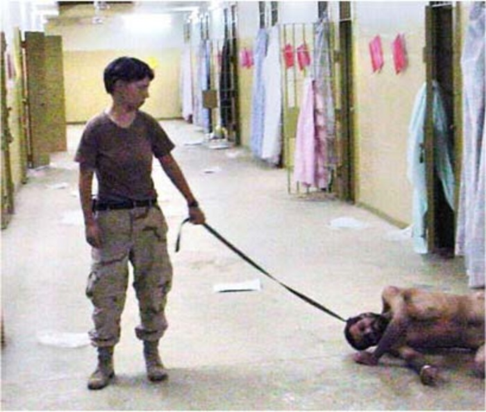 Private First Class Lynndie England holds a leash attached to an Iraqi detainee, known to guards as Gus,