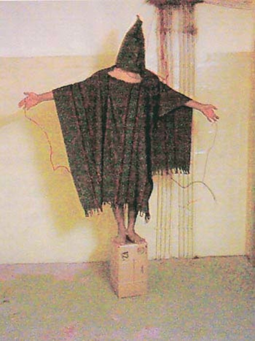 [Abdou Hussain Saad Faleh, nicknamed Gilligan by U.S. soldiers, made to stand on a box for about an hour and told that he would be electrocuted if he fell, Abu Ghraib prison, Iraq]