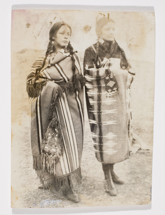 [Two young women wearing traditional Native American dress]