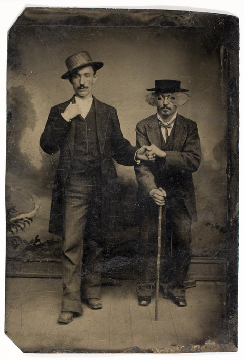[Unidentified Man Leading Man Wearing a Mask and Holding a Cane]