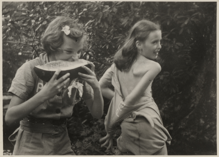 [Two unidentified girls, one eating watermelon, the other disrobing]