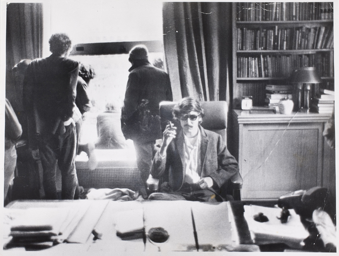 [Student activist David Shapiro sitting behind University President Kirk's desk smoking an appropriated cigar during six-day campus uprising and protest at Columbia University, New York]