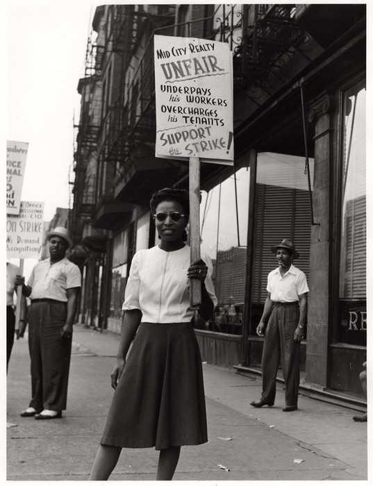 Girl in a picket line before Mid-City Realty Company in south Chicago