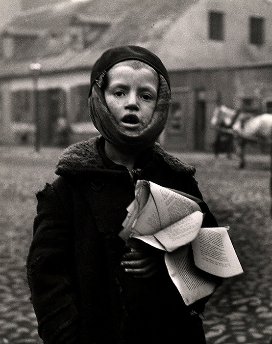 [Boy suffering from a toothache clutches a tattered schoolbook, Slonim]