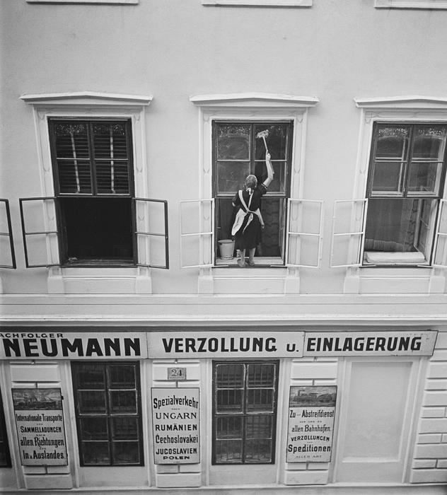 [Woman washing windows above Nachfolger Mandtler & Neumann Speditionen (Mandtler & Neumann Forwarding Agents), Ferdinandstrasse, Leopoldstadt, Vienna]