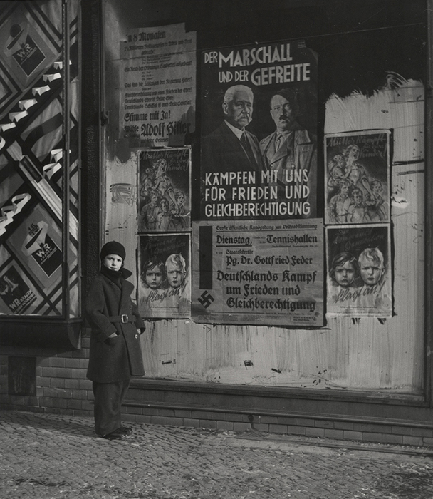 [Vishniac's daughter Mara posing in front of an election poster for Hindenburg and Hitler that reads