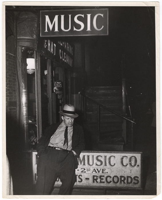 [Man sleeping in front of music store, New York]