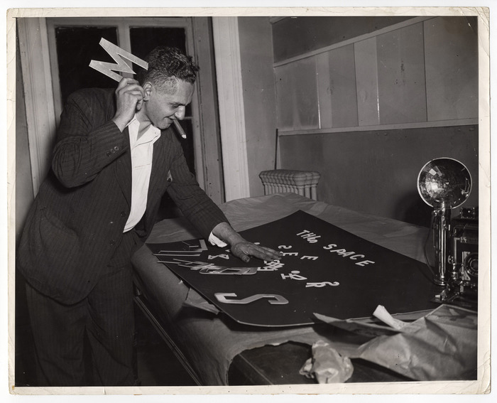 [Weegee making a sign for his Photo League exhibition