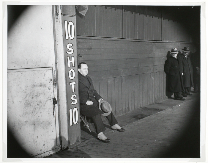 [Sunbather in front of a padlocked shooting gallery, Coney Island, Brooklyn]