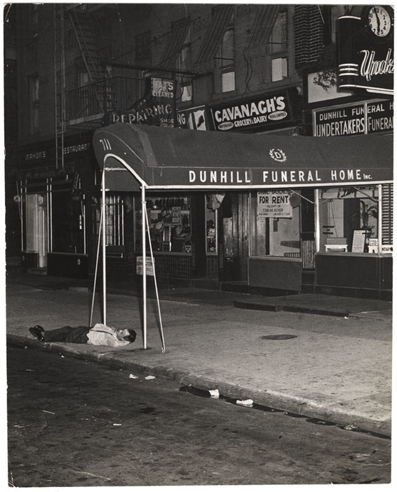 [Man sleeping on pavement in front of Dunhill Funeral Home, New York]