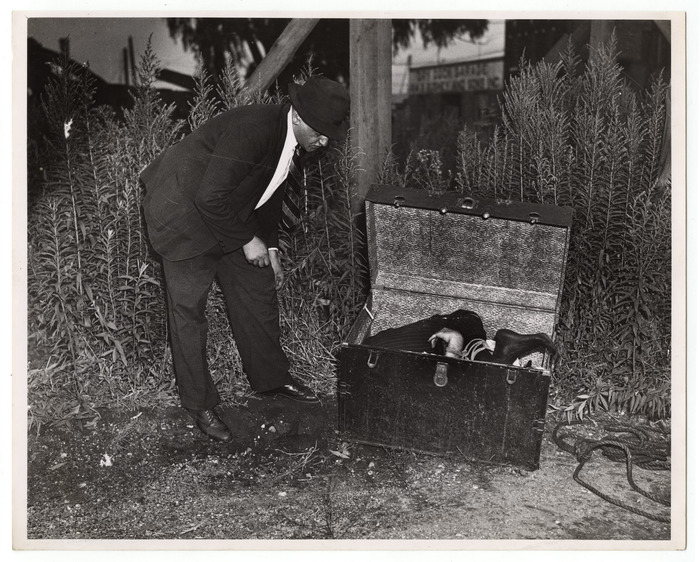 [Weegee inspecting trunk containing body of William Hessler, who had been stabbed to death, Brooklyn]