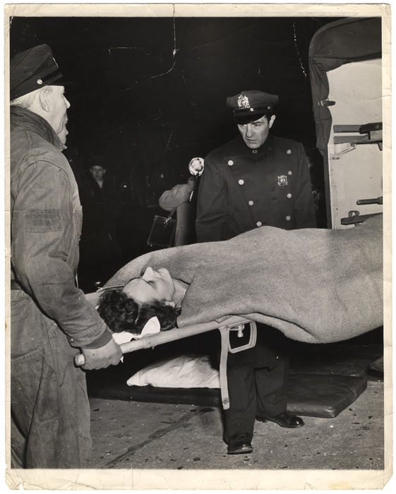 [Police officer looking at woman on stretcher]